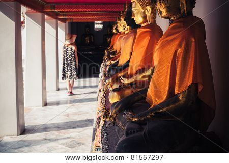 Woman Looking At Buddha Statues In Temple