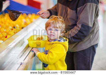 Little Cute Kid Boy Playing Game With Rubber Ducks On Fair