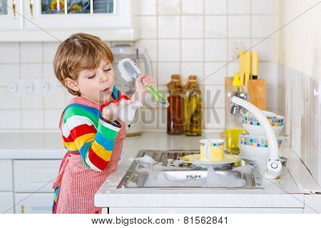Adorable Toddler Child Washing Dishes In Domestic Kitchen.
