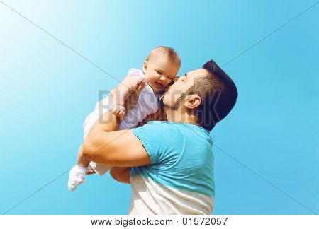 Lifestyle Family Photo Happy Father Kissing Baby Outdoors Against On Summer Sunny Blue Sky