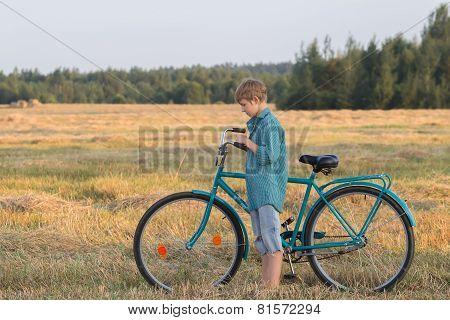 Teenager Boy Pushing Bicycle In Farm Field