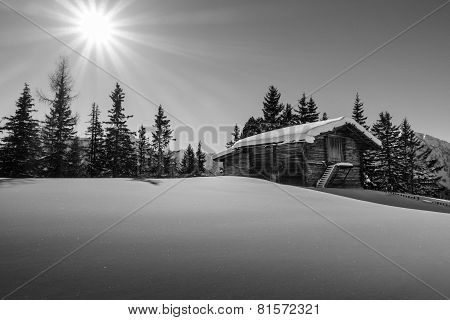 Mountain sun over the ski hut in black and white