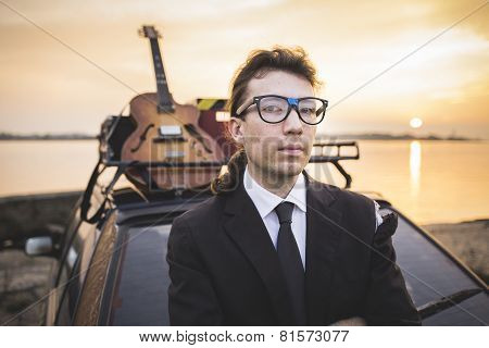 Hipter in glasses and his guitar on car rack