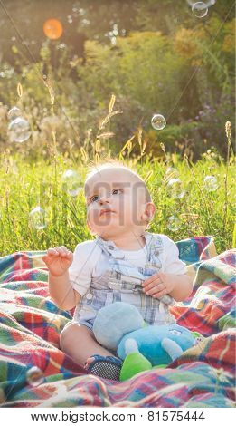 Baby sitting on plaid and playing with soap bubbles, outdoor at sunset
