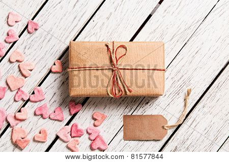 Gift box with blank gift tag and heap of small hearts on white wooden background.