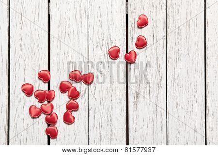 Holiday background with heap of small hearts on white wooden table.