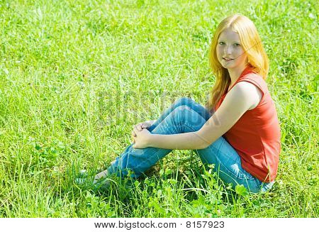 Teenager Girl  Sitting In Grass