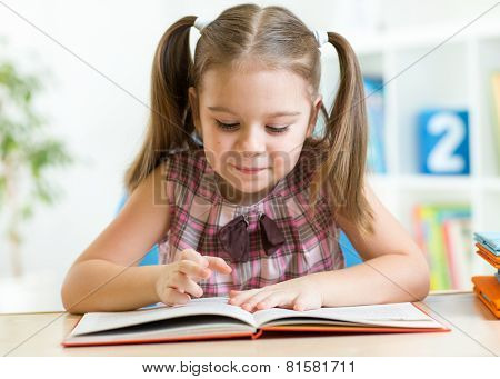 Cute kid girl reading story from big book in nursery