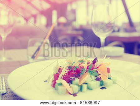 Tuna tartar with cucumber and orange on restaurant table, old film toned
