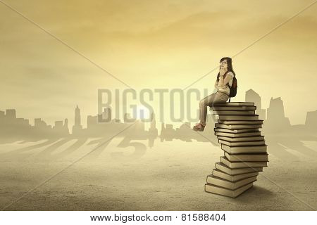 Student Sitting And Dreaming Above Book