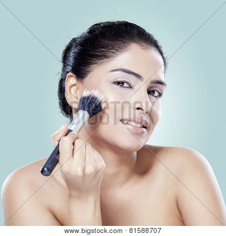 Woman Applying Makeup On Her Cheek