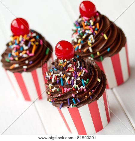 Cupcakes decorated with chocolate frosting and maraschino cherries