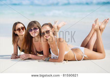 Three girls in bikini sunbathing lying on the sand of a tropical beach.