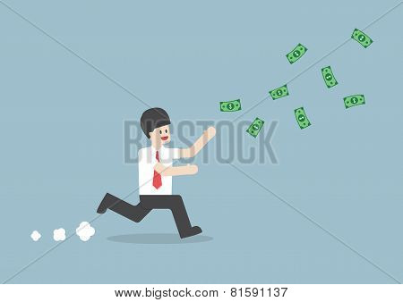 Businessman Chasing Falling Dollar Bills