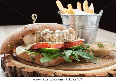 Wheat chicken sandwich burger with fried potatoes and mustard sauce. Served launch