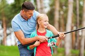 stock photo of father daughter  - Cheerful father and daughter fishing together and smiling - JPG
