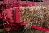 foto of hay bale  - Bale of fresh hay coming out a red hay baler - JPG