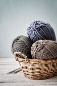 pic of coil  - Wool yarn in coils with knitting needles in wicker basket on light blue background - JPG