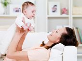 picture of newborn baby  - Beautiful young happy mother playing with her baby at home  - JPG
