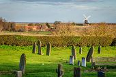 picture of graveyard  - A windmill by the Norfolk UK coast as seen from church graveyard - JPG