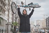 picture of beard  - Young handsome bearded man posing with his bicycle in the city streets  - JPG