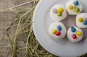 picture of easter candy  - Easter cake with coconut decorated with colored jelly beans in the shape of Easter eggs on a wooden background with a straw - JPG