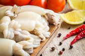picture of cuttlefish  - Raw babies cuttlefish on a cutting board with tomatoes chili peppers and lemon - JPG