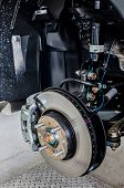 stock photo of calipers  - Front disc brake on car in process of new tire replacement - JPG