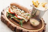 picture of cheese-steak  - Healthy wheat sandwich burger with BBQ grilled chicken steak cheese tomato rocket salad cucumber fried potato and mustard sauce served for eating on wooden board - JPG