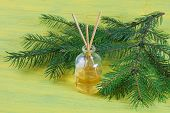 foto of diffusion  - Fragrance sticks or bottle Scent diffuser with sprig fir on wooden background - JPG