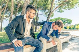 stock photo of life-support  - Young business man supporting a depressed person  - JPG