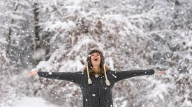foto of vivacious  - Happy vivacious woman celebrating the winter snow standing with her arms outspread in a snowy forest laughing as she watches the falling snowflakes from above - JPG