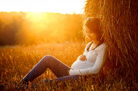 stock photo of haystacks  - Young Pregnant Woman Sitting by the Haystack at Sunset and Embracing her Belly - JPG