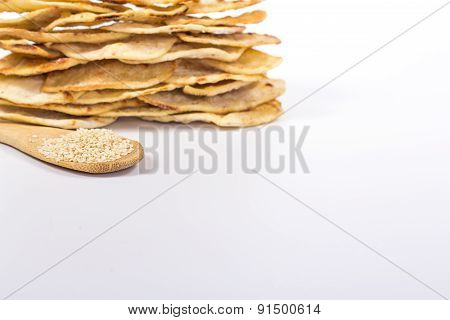 isolated stack of flat white bread and spoon with sesame seeds