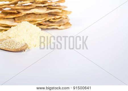 isolated stack of flat white bread, flour and spoon with sesame