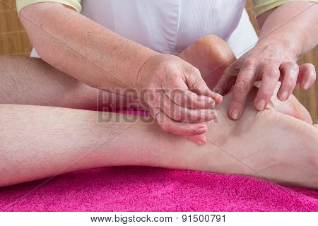 Woman Acupuncturist Prepares To Tap Needle On  Malleolus Of A Man