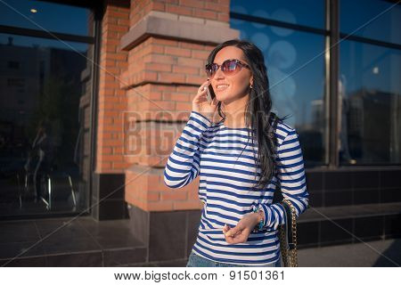 girl talking on the phone. walking through the streets of the city