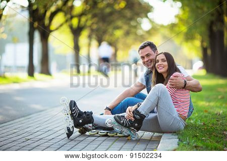 Young couple with rollers in park