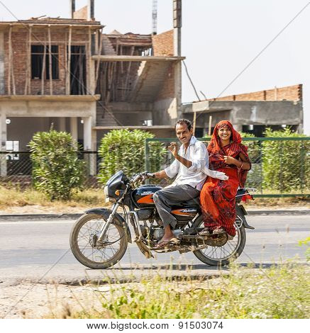 Husband With His Wife  Riding On Scooter Through Highway Street