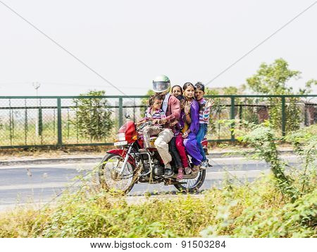 Mother, Father And Children Riding On Scooter Through  Highway Street
