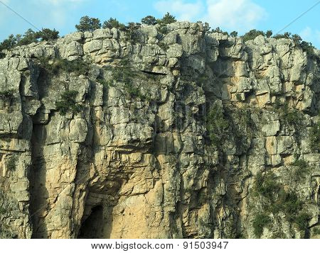 Rocky Cliff, Mountain Trees And Blue Sky