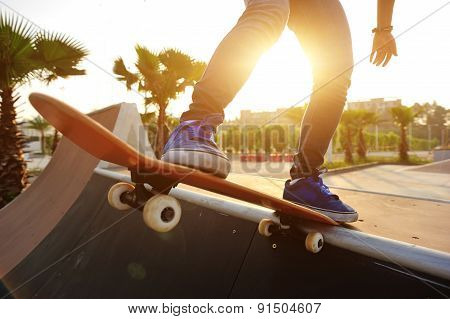 young woman skateboarding at sunrise skatepark