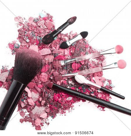 crushed eyeshadows with set of brushes isolated on white background