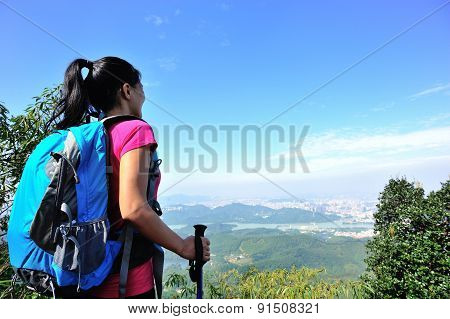 woman hiker looking into the wilderness on mountain peak