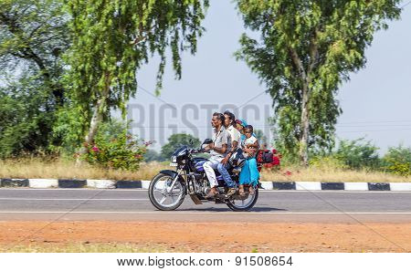 Mother, Father And Small Child Riding On Scooter Through Busy Highway