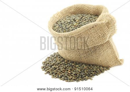 French green lentils (lentilles du Puy) in a burlap bag on a white background