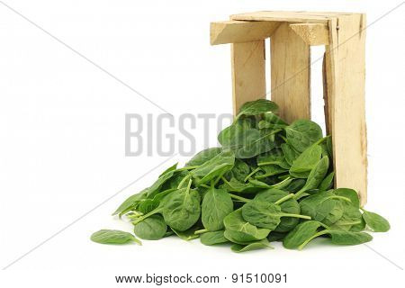 fresh spinach leaves in a wooden box on a white background