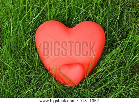 Red hearts on grass