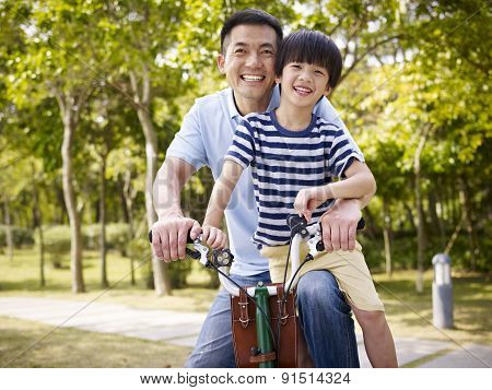 Asian Father And Son Enjoying Biking Outdoors
