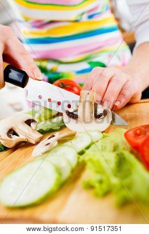 Woman's hands cutting mushroom champignon